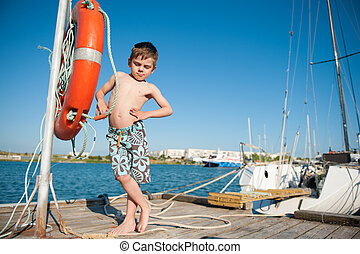 funny little healthy boy in shorts stands on the pier with sea and blue sky background