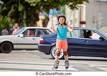 Funny Little pretty girl on roller skates in helmet riding in a park.