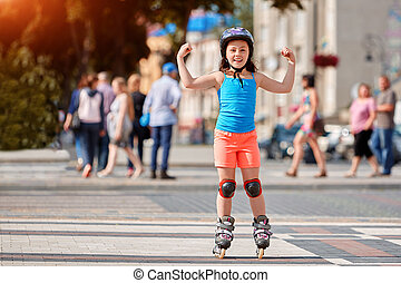 Funny Little pretty girl on roller skates in helmet riding in a park.