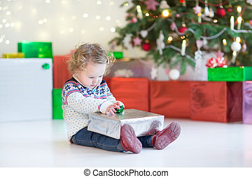 Funny little toddler girl opening her Christmas present under a