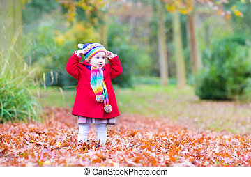 Funny little toddler girl playing in a beautiful autumn park wit