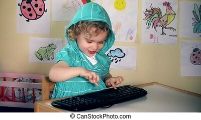 Funny lovely child girl typing computer keyboard and looking...
