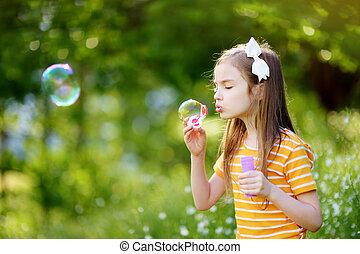 Funny lovely little girl blowing soap bubbles on a sunset outdors