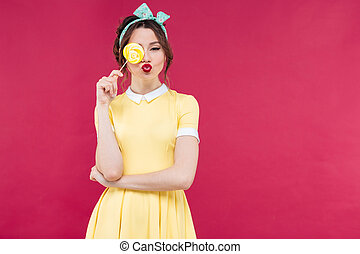 Funny lovely pinup girl covered one eye with yellow lollipop...