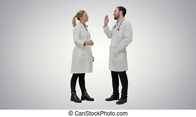 Funny male doctor kidding on female nurse give a false hi five on white background.