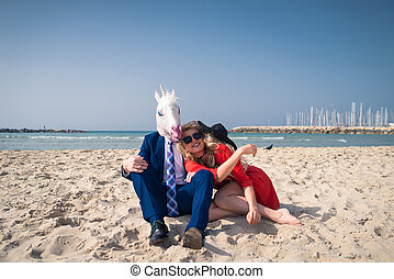 Funny man in elegant suit and horse-head mask with young woman