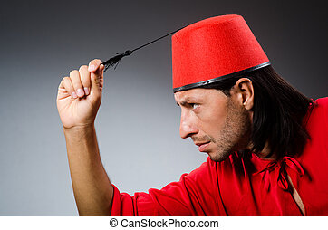 Funny man in red dress wearing fez hat