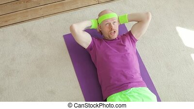 Funny man is doing abs exercises crunches at home on floor, sportive humor.