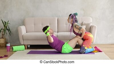 Funny man is doing abs exercises crunches at home with wife, fitness humor.
