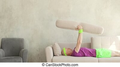 Funny man is making exercises pulling pillow lying on sofa, fitness humor.