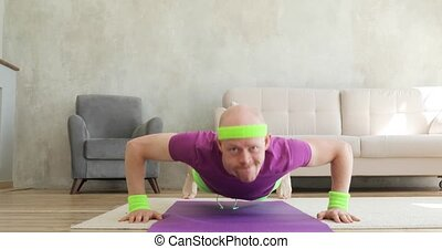 Funny man is making push-ups exercises on mat looking at camera, fitness humor.