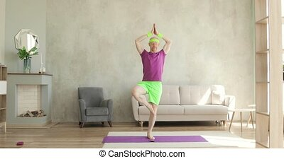 Funny man is practicing yoga standing in tree pose at home, fitness sport humor.