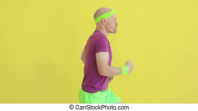 Funny man is running away from screen with bottle in hands on yellow background, side view. Sportive humor, joke, comical, mem, parody, fun behavior. Cardio training, jogging. Portrait of young guy.