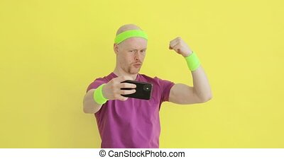 Funny man is taking picture of his biceps on smartphone on ...
