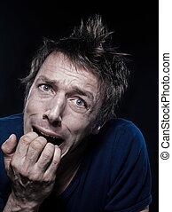 Funny Man Portrait grimacing fear - studio portrait on black...