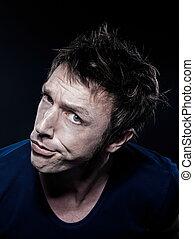 studio portrait on black background of a funny expressive caucasian man puckering distrus