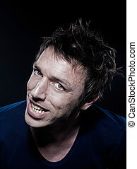 studio portrait on black background of a funny expressive caucasian man toothy smiling cheerfu