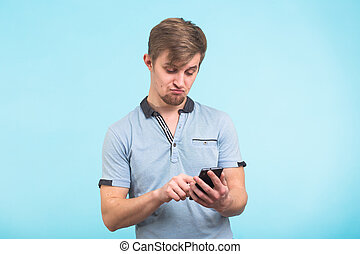 Funny man texting message on smart phone isolated on blue background. Smiling guy holding smartphone and looking at it.
