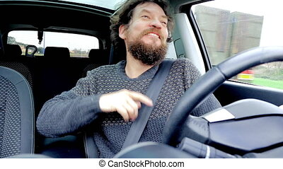 Funny man with beard singing and dancing in car slow motion