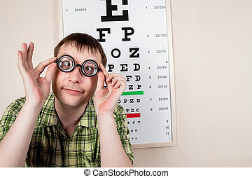 Funny manwearing spectacles in an office at the doctor