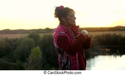 Funny mature adult woman dancing on the rock. having fun during sunset.