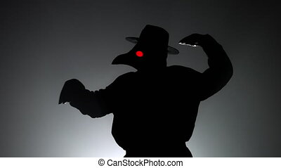 Funny meme footage of comic man in plague doctor costume with crow-like mask dancing with hands isolated on black background. Creepy mask, historical costume concept. Epidemic. High quality 4k footage