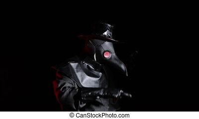 Funny meme footage of comic man in plague doctor costume with crow-like mask dancing with hands isolated on black background. Creepy mask, historical costume concept. Epidemic.