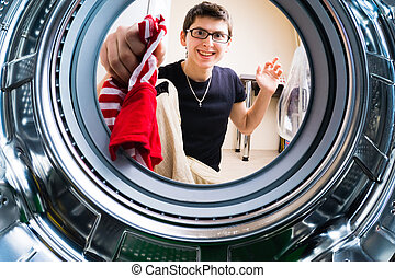 Funny men loading clothes to washing machine