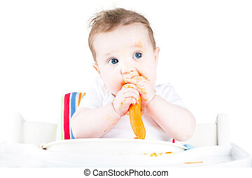 Funny messy baby eating a carrot