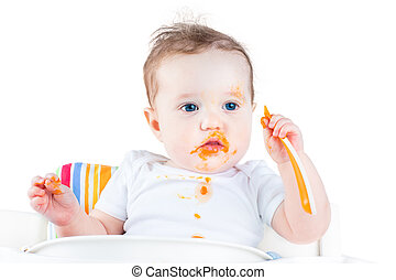 Funny messy baby eating her first solid vegetable food in a whit