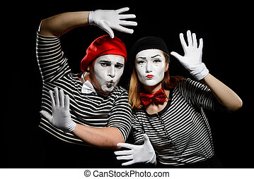 Funny mime artists on black. Striped shirts, white gloves and berets