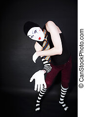 Funny mime in white gloves on black background