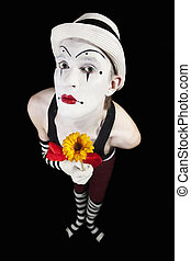Funny mime in white hat with a bouquet of flowers on a black...