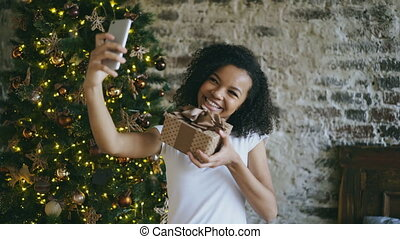 Funny african american girl taking selfie pictures on smartphone camera at home near Christmas tree