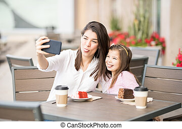 Funny mother and daughter taking selfie at cafe - Funny...