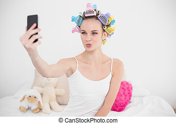 Funny natural brown haired woman in hair curlers taking a...