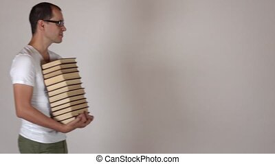 Funny nerdy man in black rim glasses carrying big stack of books against gray background. 4K shot