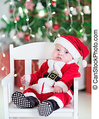 Funny newborn baby boy in a Santa outfit sitting under a...