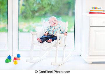 Funny newborn baby boy in a white rocking chair next to a big wi