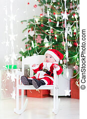 Funny newborn baby boy in Santa costume sitting in a white rocki