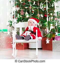 Funny newborn baby dressed as Santa relaxing in a white rocking