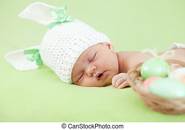 funny newborn baby dressed in Easter bunny cap with eggs -...