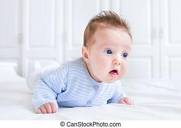 Funny newborn baby enjoying her tummy time in a white nursery