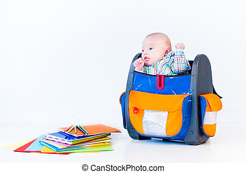Funny newborn baby in a school backpack on white background