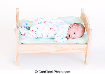 Funny newborn baby in a toy bed
