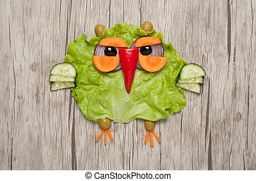 Funny owl made of vegetables on wooden background