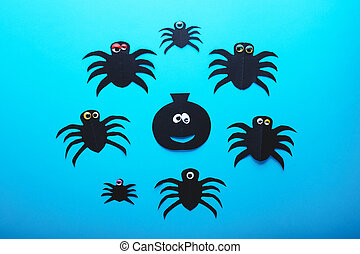 Funny paper spiders and pumpkin with eyes on a blue background. Halloween decorations concept. Happy Halloween day. Flat lay, top view. Party invitation, celebration.