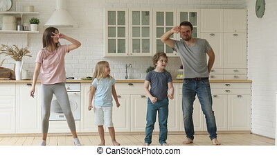 Funny parents and cute children having fun dancing in kitchen