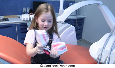 Little girl having fun in dentist%u2019s office playing with a jaw