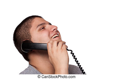 A young man listens on the telephone with a huge happy smile on his face.